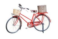 Vecchia bicicletta d'annata rossa con i canestri del rattan isolati sulle sedere bianche Fotografie Stock Libere da Diritti