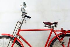 Vecchia bicicletta rossa e vecchia parete del cemento immagine stock