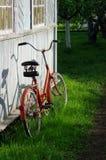 Vecchia bicicletta rossa vicino alla vecchia parete di legno Fotografia Stock