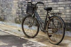 Vecchia bicicletta rustica che pende contro un muro di mattoni Fotografie Stock Libere da Diritti