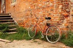 Vecchia bicicletta sui precedenti dei mura di mattoni rossi Immagini Stock Libere da Diritti