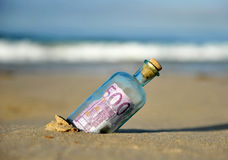 Vecchia bottiglia di vetro con la banconota dell'euro 500 dentro, sabbia della spiaggia Fotografie Stock