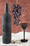 Vecchia bottiglia di vino con una coppa piena di vino, il mazzo di uva ed il sughero Fotografie Stock Libere da Diritti