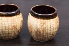 Vecchia brocca su fondo marrone tazze di t? marroni della porcellana Latte ceramiche Piccoli vasi Piatti dell'argilla di Brown i  fotografia stock