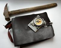 Vecchia bussola geologica, un martello e borsa su fondo grigio Immagini Stock Libere da Diritti