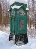 Vecchia cabina telefonica in foresta sotto neve immagini stock libere da diritti