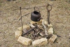 Vecchia caldaia arrugginita sopra fuoco aperto Immagine Stock