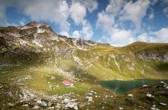 Vecchia capanna dal lago alpino il giorno soleggiato Fotografia Stock