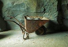 Vecchia carriola arrugginita con minerale metallifero alla miniera alla parete di pietra Fotografia Stock