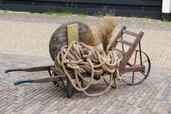 Vecchia carriola di legno caricata con la corda Fotografia Stock