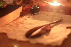 Vecchia carta con la piuma a penna ed inchiostro, una candela e una bibbia su scrittura di legno della tavola immagini stock libere da diritti