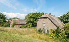 Vecchia casa abbandonata dell'azienda agricola con il tetto ricoperto di paglia Immagine Stock