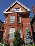 Vecchia casa con mattoni a vista con il grande timpano immagini stock