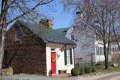 Vecchia casa con mattoni a vista con una porta rossa Fotografia Stock