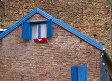 Vecchia casa con mattoni a vista di Brown con gli otturatori di legno della finestra Fotografia Stock