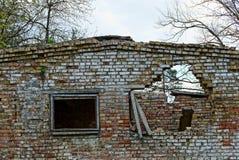 Vecchia casa con mattoni a vista rovinata con le finestre rotte contro il cielo Immagini Stock Libere da Diritti