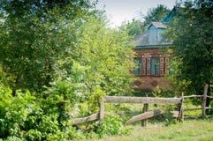 Vecchia casa del villaggio dietro il recinto Fotografie Stock Libere da Diritti