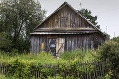 Vecchia casa di legno con il recinto erboso Povero palazzo del villaggio con op Immagini Stock