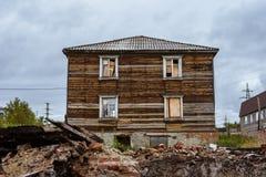 Vecchia casa di legno cruda abbandonata con guidare-in finestre fotografia stock