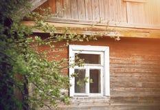 Vecchia casa di legno del villaggio con una struttura bianca sulla finestra immagini stock libere da diritti