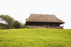Vecchia casa di legno sola del villaggio sulla collina immagini stock libere da diritti