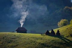 Vecchia casa di legno sola su una collina della montagna con fumo contro il cielo nuvoloso Fotografia Stock Libera da Diritti
