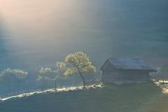 Vecchia casa di legno sola su una collina della montagna con fumo contro il cielo nuvoloso Fotografie Stock