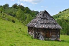Vecchia casa di legno sola su una collina della montagna contro il cielo nuvoloso Fotografie Stock Libere da Diritti