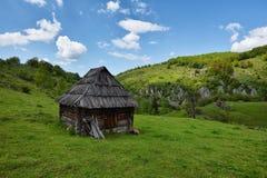 Vecchia casa di legno sola su una collina della montagna contro il cielo nuvoloso Immagine Stock Libera da Diritti