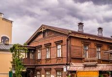 Vecchia casa di legno in una città moderna Immagine Stock Libera da Diritti