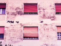 Vecchia casa di lerciume con i ciechi persiani fotografia stock
