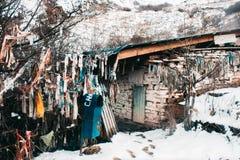 Vecchia casa di pietra con l'attaccatura degli stracci variopinti fotografia stock