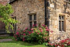 Vecchia casa di pietra inglese tradizionale con flusso variopinto del geranio immagini stock libere da diritti