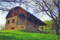 Vecchia casa di pietra sul pendio di collina Fotografia Stock