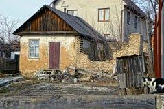 Vecchia casa e un muro di mattoni rotto Fotografia Stock