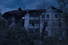 Vecchia casa frequentata abbandonata con l'atmosfera scura di orrore nella luce della luna immagine stock