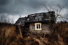 Vecchia casa frequentata rovinata sul campo vuoto con cielo blu drammatico fotografia stock
