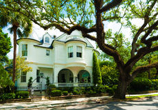 Vecchia casa padronale adorabile sotto il cielo soleggiato sulla via suburbana calma Immagine Stock