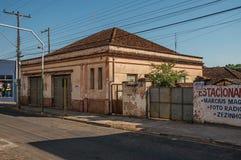 Vecchia casa superata e parete con il cartello dipinto in via vuota sul tramonto a São Manuel fotografie stock