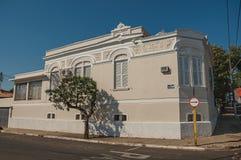 Vecchia casa urbana d'angolo decorata in una via vuota con gli alberi sul marciapiede a São Manuel fotografia stock
