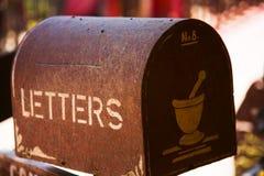 Vecchia cassetta delle lettere marrone arrugginita con il testo della scatola di lettera, nella circostanza consumata, all'aperto immagini stock