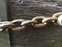 Vecchia catena arrugginita su legno fotografia stock libera da diritti