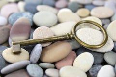 Vecchia chiave d'ottone su un Pebble Beach Fotografie Stock
