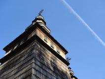Vecchia chiesa ortodossa di legno, costruendo con il tetto di legno e la traccia bianca dall'aereo nel cielo blu fotografia stock libera da diritti