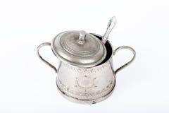 Vecchia ciotola di zucchero con il coperchio ed il cucchiaio con i punti di ruggine su un bianco Fotografia Stock Libera da Diritti