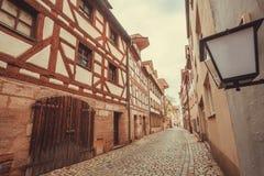 Vecchia città con le vie di pietra cobbled, le case tradizionali e le lanterne in Baviera immagini stock libere da diritti