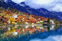 Vecchia citt? e montagne delle alpi che riflettono nel lago, Svizzera immagine stock