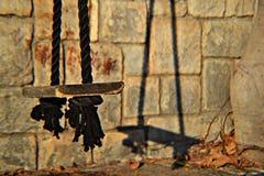 Vecchia corda invecchiata del nero del briciolo dell'oscillazione che appende sulla parete di pietra fotografie stock