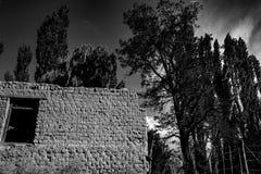 Vecchia costruzione abbandonata situata nella campagna fra gli alberi alti e le tracce della sporcizia fotografia stock