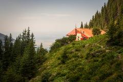 Vecchia costruzione dell'ostello con il tetto rosso nelle montagne della Romania fotografia stock